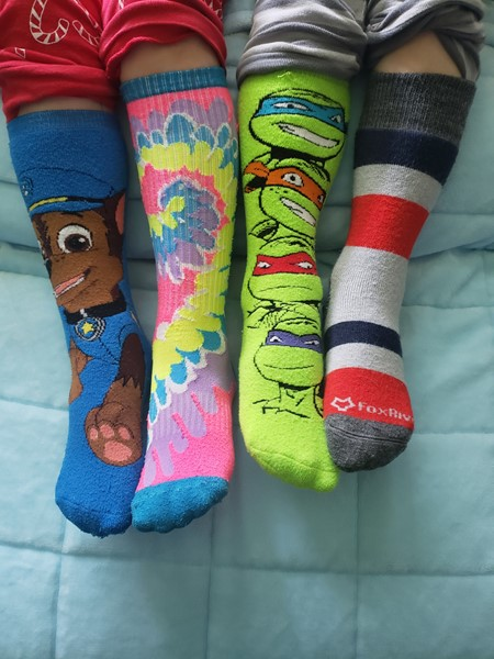 Four family members wearing unique socks. Picture is just of feet.