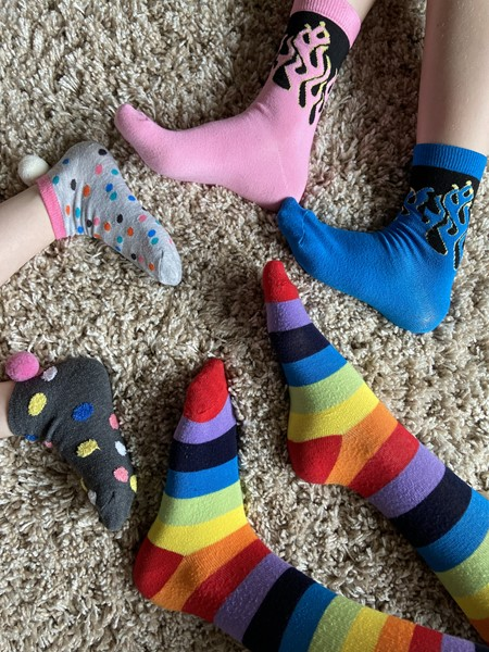 Family members wearing unique socks. Picture is just of feet.