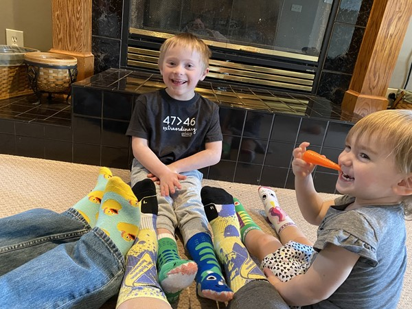 Family wearing unique socks and two of their children in the picture also wearing unique  socks.