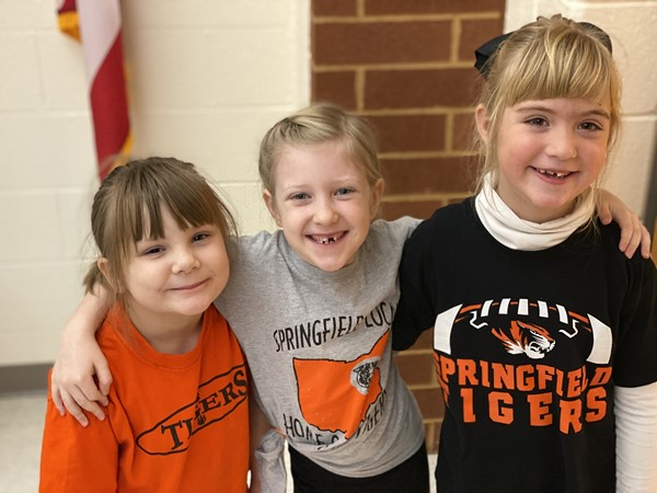 Three elementary students wearing Tigers shirts.
