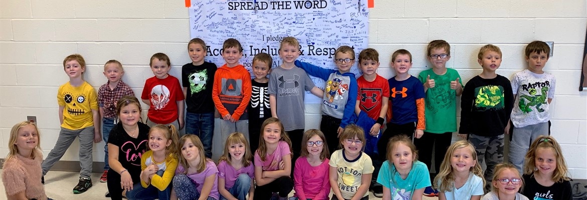 SLES students signed a pledge to accept, include and respect people of all abilities. Group of students standing in front of banner they signed.
